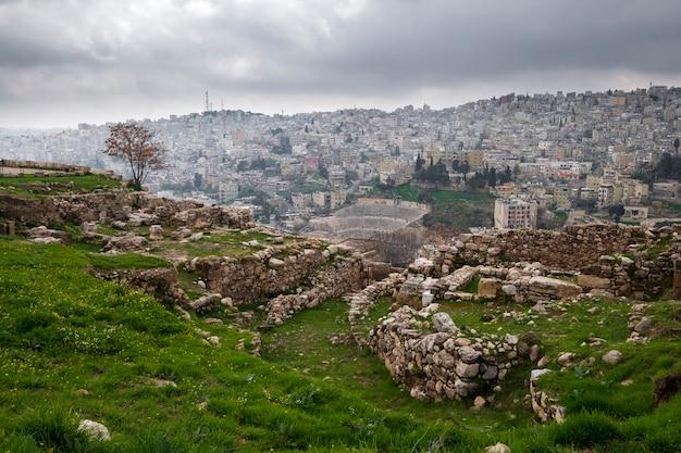 Les ruines de la citadelle sur la ville d'amman et le théâtre romain de jordanie sur un jour nuageux de printemps