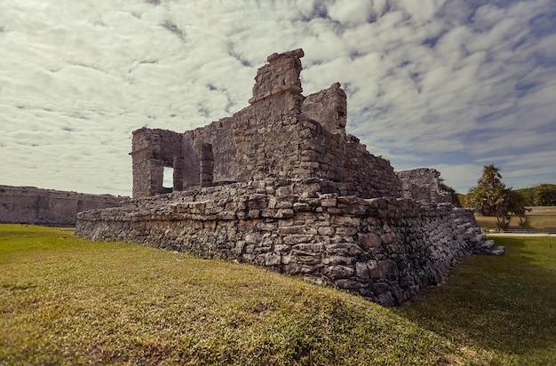 Ruines du bâtiment maya immergé dans un pré vert : vue de certaines parties du complexe maya à tulum au mexique