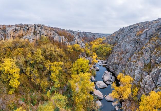 Un ruisseau coule dans le canyon aktovsky, en ukraine. arbres d'automne et gros rochers autour.