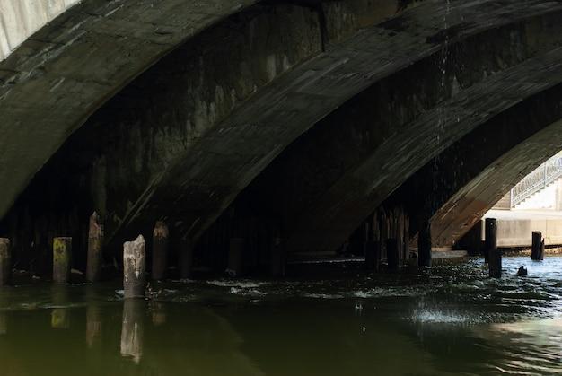 Le ruisseau coule sous le vieux pont avec des voûtes voûtées et les restes de pieux en bois