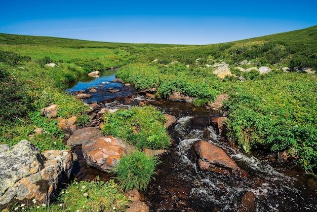 Ruisseau de montagne avec de gros rochers près de pré vert en journée ensoleillée.