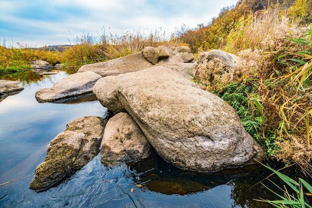 Un ruisseau rapide, peu profond et propre coule parmi de grosses pierres lisses et humides entourées de grands morceaux secs