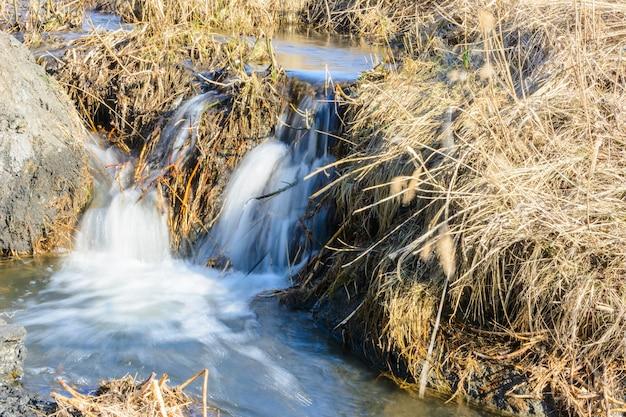 Des ruisseaux printaniers tant attendus coulent sur des ravins et des collines par une journée ensoleillée. rapides d'eau et cascades de ruisseaux parmi l'herbe sèche. beau paysage de printemps.