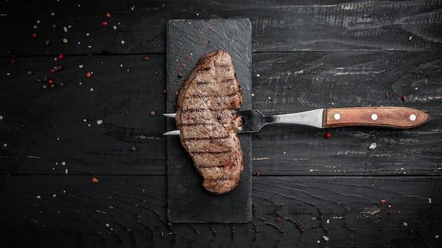 Rump steak sur fourche sur fond de bois foncé. bannière, lieu de recette de menu pour le texte, vue de dessus.