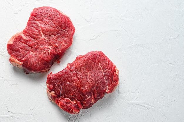 Rump steak, viande de boeuf cru biologique de ferme fond texturé blanc. espace de vue de dessus pour le texte.