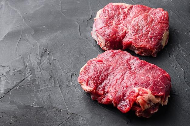 Rump steaks bio sur fond noir, vue latérale avec un espace pour le texte.