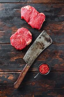 Rump steaks crus avec couperet de boucher américain sur fond de bois ancien foncé, vue de dessus.