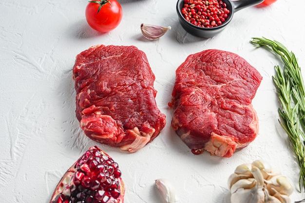 Rumpsteak cru, viande de bœuf fermier aux assaisonnements, romarin, ail, grenat. fond texturé blanc. vue de côté.