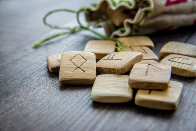 Runes anciennes, sac en toile avec broderie sur fond de bois ancien vintage. mise au point sélective.
