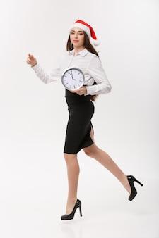 Rush time concept - belle jeune femme caucasienne en cours d'exécution avec horloge isolé sur blanc.