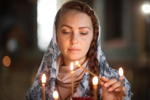 Russe belle femme caucasienne aux cheveux rouges et une écharpe sur la tête est dans l'église orthodoxe