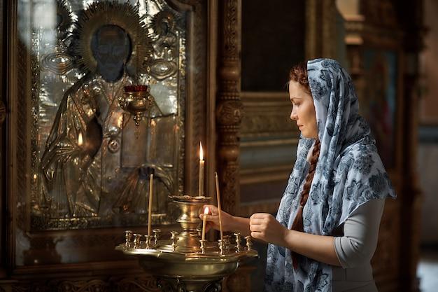 Russe belle femme de race blanche aux cheveux rouges et un foulard sur la tête est dans l'église orthodoxe, allume une bougie et prie devant l'icône.