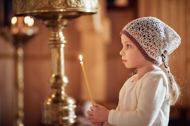 Russe petite fille dans un foulard sur la tête se dresse dans une église orthodoxe