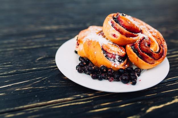 Rustique avec tarte aux baies actuelle noire sur table en bois noir.