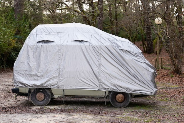 Rv camping-car voiture recouverte de housse de protection grise par townhouse pour temps humide dans un parking ville