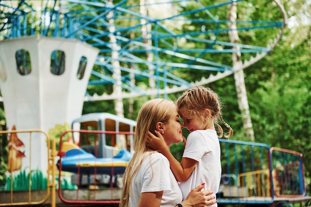 S'aimer les uns les autres. joyeuse petite fille sa mère passe un bon moment dans le parc ensemble à proximité des attractions.