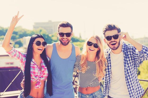 S'amuser avec des amis. groupe de jeunes joyeux se liant les uns aux autres et regardant la caméra en se tenant debout sur le toit