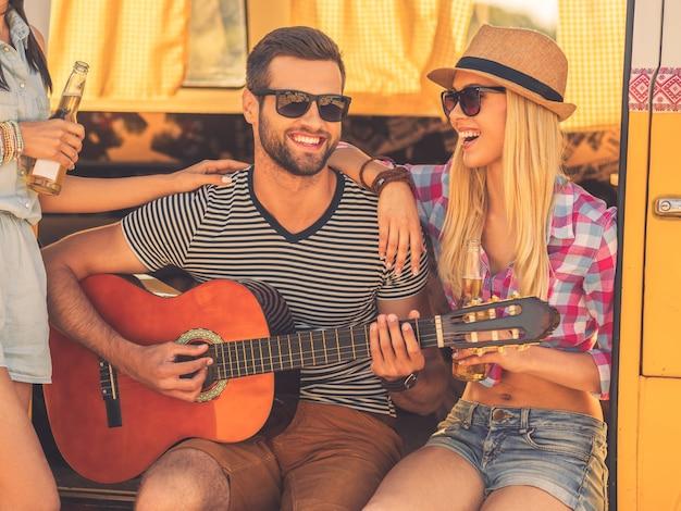 S'amuser après un long voyage sur la route. beau jeune homme assis dans un minibus et jouant de la guitare tandis que deux jeunes femmes se lient à lui