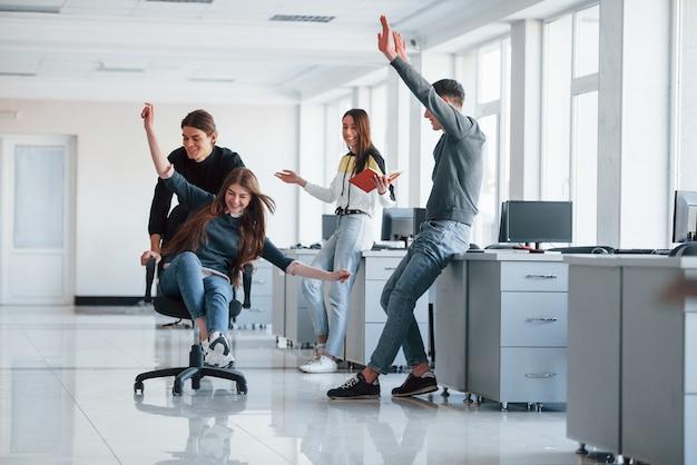 S'amuser au bureau. les jeunes font une pause et conduisent en utilisant un siège