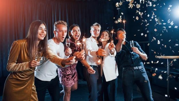 S'amuser Avec Des Cierges Magiques. Des Confettis Sont Dans L'air. Groupe D'amis Joyeux Célébrant Le Nouvel An à L'intérieur Avec Des Boissons à La Main. Photo Premium