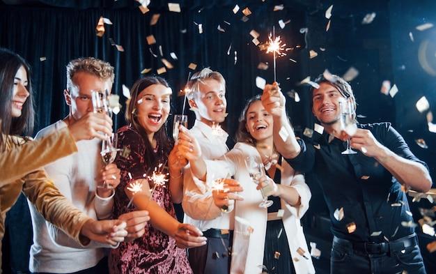 S'amuser avec des cierges magiques. des confettis sont dans l'air. groupe d'amis joyeux célébrant le nouvel an à l'intérieur avec des boissons à la main.