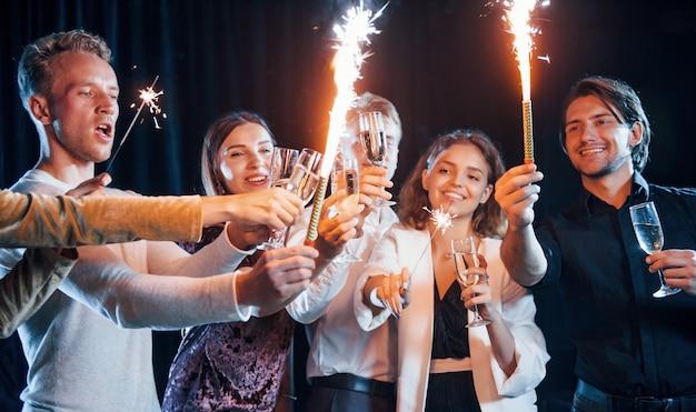 S'amuser avec des cierges magiques. groupe d'amis joyeux célébrant le nouvel an à l'intérieur avec des boissons à la main.