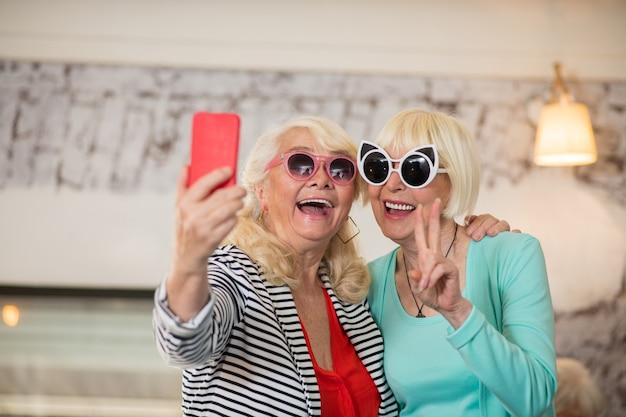 S'amuser. deux femmes excitées seniors faisant du selfie et s'amusant