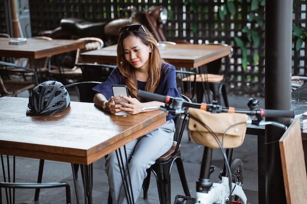 S'amuser femme asiatique à l'aide de smartphone lors d'une pause au café