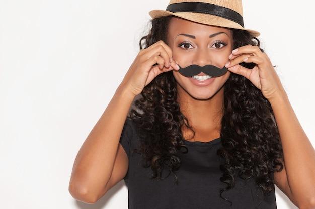 S'amuser avec la moustache du visage. joyeuse jeune femme africaine au chapeau funky tenant une fausse moustache sur son visage et regardant la caméra en se tenant debout sur fond blanc