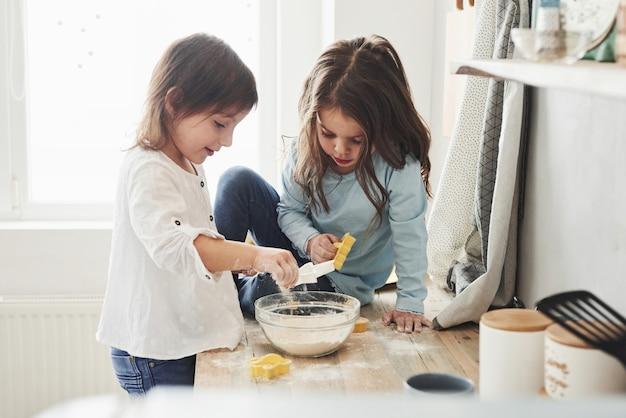 S'amuser pendant le processus. amis préscolaires apprenant à cuisiner avec de la farine dans la cuisine blanche