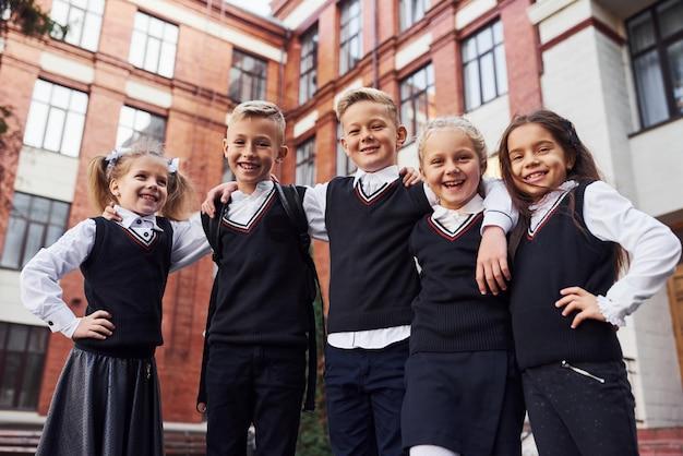 S'amuser et s'embrasser. groupe d'enfants en uniforme scolaire qui est à l'extérieur ensemble près du bâtiment de l'éducation.