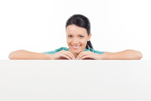 S'appuyant sur l'espace de copie. belle jeune femme se penchant à l'espace de copie et souriant tout en se tenant isolé sur blanc