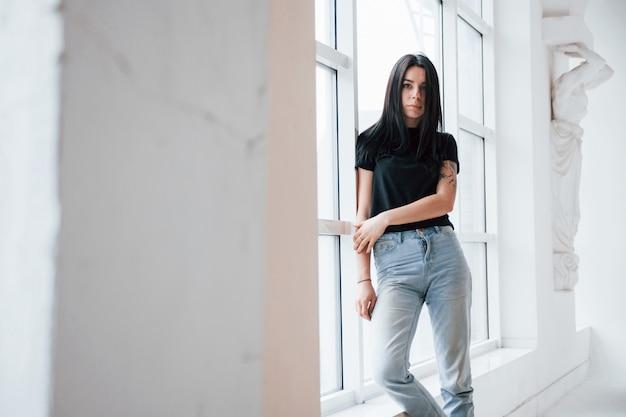 S'appuyant sur la fenêtre. une jeune adolescente brune a une séance photo en studio pendant la journée