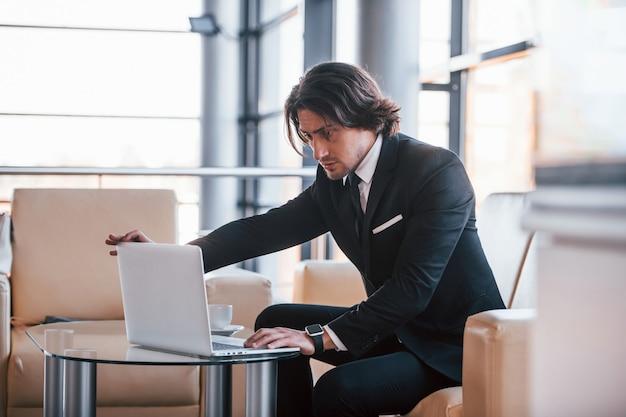 S'assoit sur le canapé avec un ordinateur portable. portrait de beau jeune homme d'affaires en costume noir et cravate.