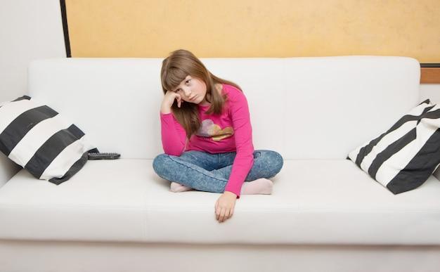 S'ennuyer jeune fille s'asseoir sur le canapé
