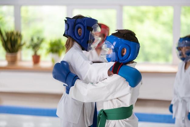 S'entraîner au combat. garçon et fille portant des casques de protection pratiquant le combat ensemble