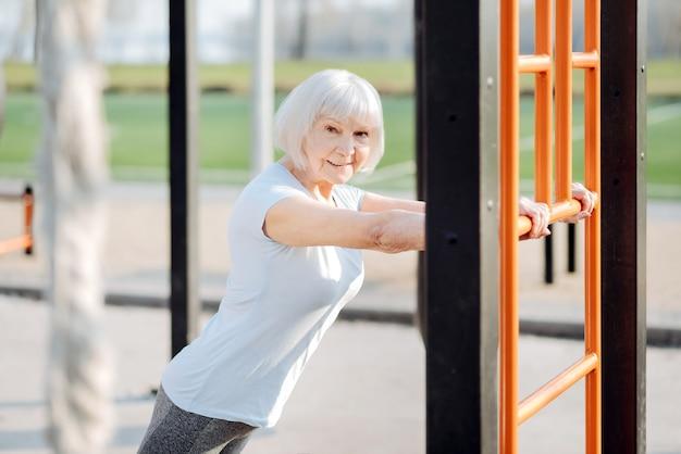 S'entraîner dur. femme blonde joyeuse portant des vêtements de sport et exerçant en plein air