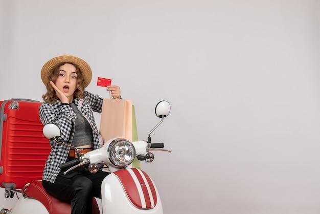 S'est Demandé Jeune Femme Sur Cyclomoteur Holding Card Sur Gray Photo gratuit
