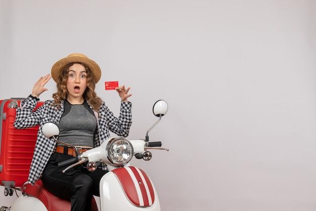 S'est Demandé Jeune Femme Sur Cyclomoteur Holding Card Sur Gris Isolé Photo gratuit