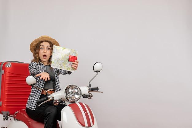 S'est Demandé La Jeune Femme Sur Le Cyclomoteur Tenant La Carte Et La Carte Sur Le Gris Photo gratuit