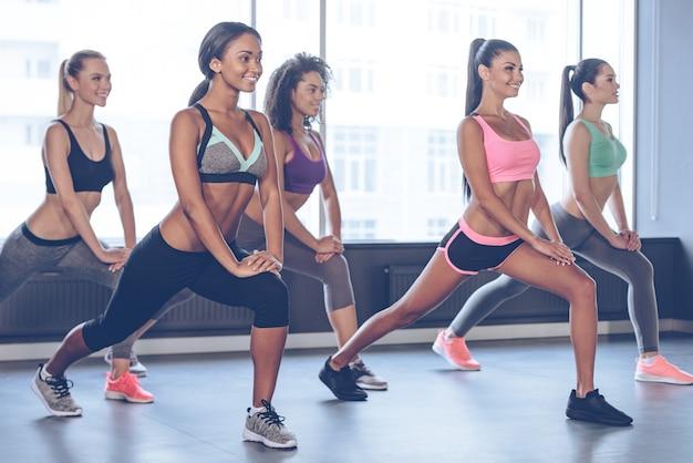 S'étirer après une bonne séance d'entraînement. belles jeunes femmes avec des corps parfaits en vêtements de sport faisant de l'exercice avec le sourire tout en se tenant devant la fenêtre de la salle de sport