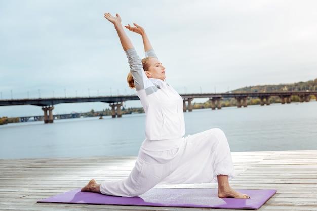 S'étirer à l'extérieur. joyeusement à la femme effectuant des exercices pour étirer ses muscles