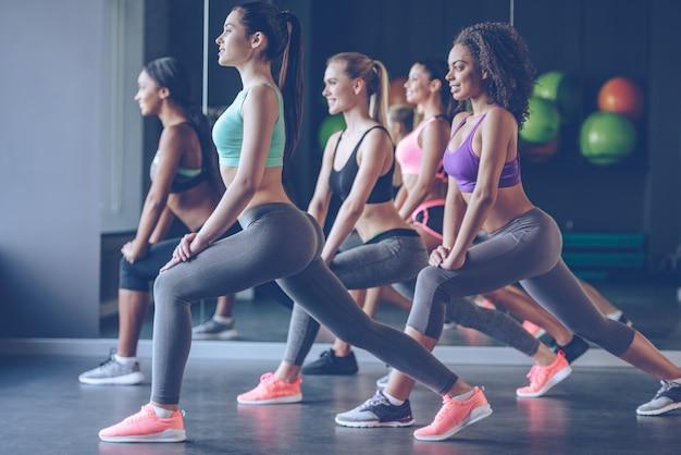 S'étirer avec le sourire. vue latérale de belles jeunes femmes avec des corps parfaits en vêtements de sport faisant de l'exercice avec le sourire au gymnase