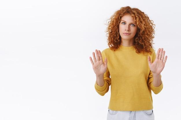 S'il te plaît, arrête, reste loin de moi. une femme bouclée rousse affirmée sait ce qu'elle veut, lève les bras en signe d'interdiction, mouvement de refus, désapprobation de la tête, souriante, ne veut pas participer, mur blanc