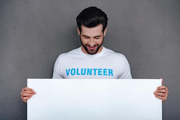 S'il vous plaît, aidez la communauté! jeune homme confiant en t-shirt bénévole tenant un tableau blanc et le regardant avec le sourire en se tenant debout sur fond gris