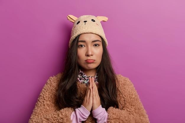 S'il vous plaît, pardonnez-moi. triste femme métisse demande de l'aide, garde les paumes dans le geste de prière, porte un chapeau d'adolescent drôle, manteau d'hiver