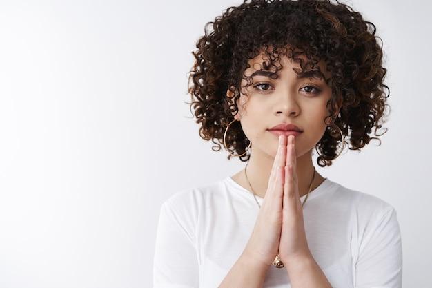 S'il vous plaît vous en suppliez. une jeune fille séduisante aux cheveux bouclés, à l'air sérieux, presse les paumes ensemble, supplication, geste de prière, demandant de l'aide, a besoin d'une offre, espère que la main d'un ami, debout, fond blanc