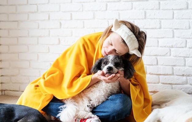 S'occuper d'un animal. drôle jeune femme souriante en plaid jaune assis avec ses chiens lisant un livre
