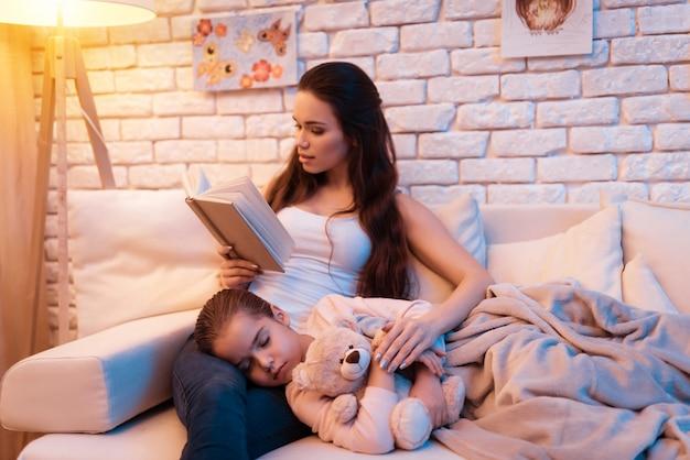 Sa fille dort chez sa mère pendant qu'elle lit un livre