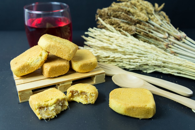 Sablé à l'ananas ou gâteau à la tarte à l'ananas avec de la confiture d'ananas sur une petite palette en bois. pâtisserie taïwanaise traditionnelle sucrée contenant du beurre. fruit. dessert.